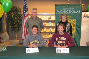 Seniors Ty DeBonis and Adrian Ell sign their letters of intent to play golf and volleyball, respectively, at the collegiate level next year. Athletic Director Rob Heise and Principal Patty Beckert were active in ceremony to honor them in library on Nov. 9.